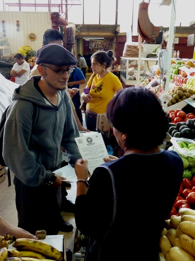 Pako shares a flyer for the Carnaval del Maíz with a vendor. Photo by author.